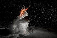 Bemannen Sie atemberaubend Snowboarding nachts unter dem Schnee stockbild