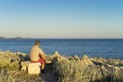Bemannen Sie auf der Bank draußen sitzen, die Meer im Sonnenuntergang betrachtet Lizenzfreie Stockfotografie