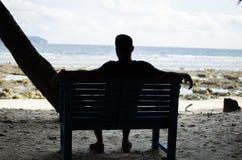 Bemannen Sie auf einer Bank allein sitzen nahe Küste stockbild