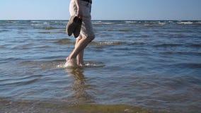 Bemannen Sie auf seichtes Wasser durch das Meer auf dem Sandstrand von links nach rechts gehen stock video