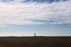 Bemannen Sie aufpassenden Horizont in einer Wüste oder in einem Strand Stockfoto