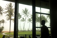Bemannen Sie aufpassenden Monsun- und Kokosnussbaum auf dem Strand, der im Th durchbrennt lizenzfreie stockfotos
