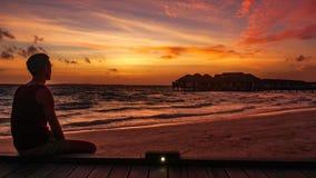 Bemannen Sie aufpassenden schönen Sonnenuntergang über dem Indischen Ozean auf Malediven-Urlaubsinsel stockfotografie