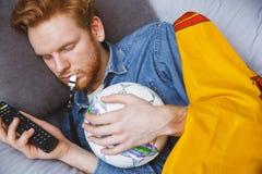 Bemannen Sie aufpassenden Sport auf Fernsehzu hause alleinschlafennahaufnahme stockbilder