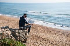 Bemannen Sie aufpassenden Stadtplan des Reisenden bei der Entspannung nahe Ozean während seiner Reise Stockfotografie