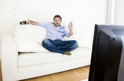 Bemannen Sie aufpassendes Fernsehen am Wohnzimmersofa mit der Fernbedienung, die okayhandzeichen gebend lächelt Stockbild