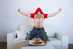 Bemannen Sie aufpassendes Fußballspiel im Fernsehen im Teamtrikot, welches das verrücktes glückliches Springen des Ziels auf Sofa Stockfoto