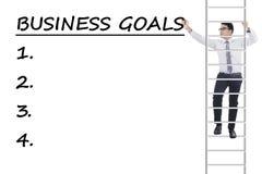 Bemannen Sie Aufstiegsleiter und schreiben Sie Unternehmensziele Stockfoto