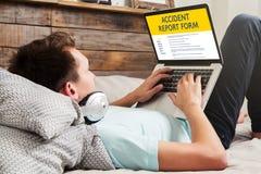 Bemannen Sie ausfüllen eine Unfallberichtform in einer Laptop-Computer stockfotos