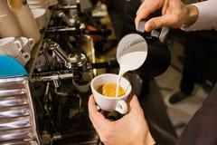 Bemannen Sie auslaufende Milch in den Kaffee, der Espresso macht Stockbild