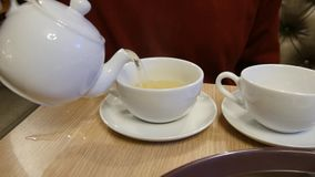 Bemannen Sie auslaufenden Tee in eine Schale stock video footage