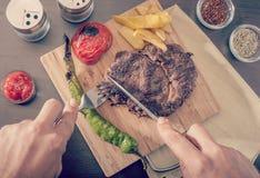 Bemannen Sie Ausschnitt und das Essen eines gegrillten Rindfleischsteaks lizenzfreie stockfotografie