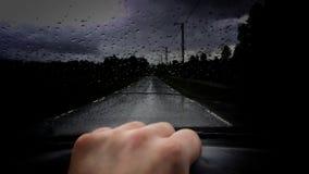 Bemannen Sie Autofahren auf öffentlicher Straße während des schweren Niederschlags mit Wassertröpfchen auf Windschutzscheiben- un Lizenzfreie Stockfotos
