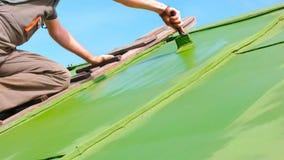 Bemannen Sie bürstende grüne Farbe auf das Dach stockfoto