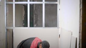 Bemannen Sie Bedeckungsmetallbau der Wand mit Platten auf Baustelle stock video