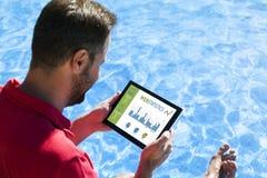 Bemannen Sie Beratungsnetzstatistiken mit einer Tablette beim Sitzen im Swimmingpoolrand Lizenzfreies Stockbild