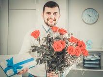 Bemannen Sie bereites, Blumen und Geschenk am Feiertag darzustellen Stockfoto