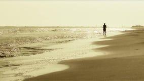Bemannen Sie Betrieb auf dem Strand am Sonnenuntergang