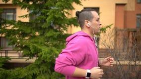 Bemannen Sie Betrieb im ausbildenden Waldholz und betrachten Sie intelligente Uhren Mannlaufen im Freien stock footage