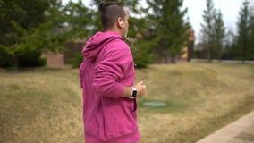 Bemannen Sie Betrieb im ausbildenden Waldholz und betrachten Sie intelligente Uhren Mannlaufen im Freien stock video