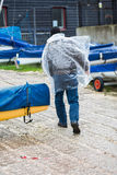 Bemannen Sie Betrieb im Regen, der einen Plastikponcho trägt Stockfotos
