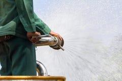 Bemannen Sie Bewässerungsanlagen auf Wasserwagen im Park lizenzfreie stockfotografie