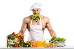 Bemannen Sie Bodybuilder in weißem Toque blanche und kochen Sie schützendes Schutzblech stockfoto