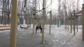 Bemannen Sie Bodybuildertraining crossfit Übung auf Sportplatz im Winterpark stock footage