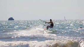 Bemannen Sie das übende Kitesurfing im Meer an einem sonnigen Tag stock footage