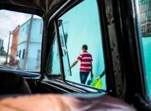 Bemannen Sie das Überschreiten durch ein offenes Oldtimerfenster in Kuba Lizenzfreie Stockbilder