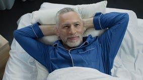 Bemannen Sie das Aalen im Bett, das an der neuen orthopädischen Matratze, bequemen Schlaf sich freut Stockfotografie