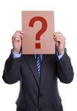 Bemannen Sie das Abdecken seines Gesichtes mit einem Fragezeichenzeichen Lizenzfreie Stockfotos