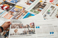 Bemannen Sie das Ablesen über opposants und Anhänger über Zeitungen Stockfotos