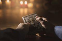 Bemannen Sie das Ablesen der heiligen Bibel und das Beten in der Kirche stockfotos