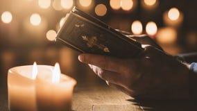Bemannen Sie das Ablesen der heiligen Bibel und das Beten in der Kirche lizenzfreie stockfotografie