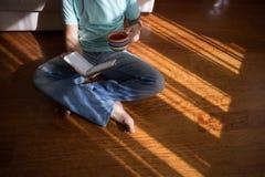 Bemannen Sie das Ablesen des alten Buches des gebundenen Buches, das zu Hause in seinen Händen, auf dem braunen Boden hält Inländ Lizenzfreies Stockfoto