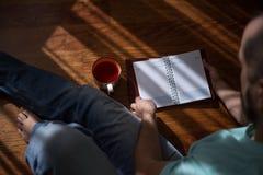 Bemannen Sie das Ablesen des alten Buches des gebundenen Buches, das zu Hause in seinen Händen, auf dem braunen Boden hält Inländ Stockfotos