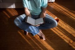 Bemannen Sie das Ablesen des alten Buches des gebundenen Buches, das zu Hause in seinen Händen, auf dem Bretterboden hält Inländi Stockfoto