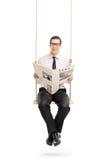 Bemannen Sie das Ablesen einer Zeitung, die auf einem Schwingen setzt Lizenzfreies Stockbild