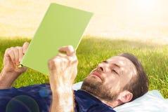 Bemannen Sie das Ablesen eines Buches, das im Garten im Freien ist Stockbild