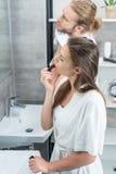 Bemannen Sie das Abwischen des Gesichtes während seine Frau, die morgens roten Lippenstift im Badezimmer anwendet Stockbild