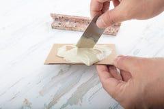 Bemannen Sie das Addieren des Klebers ein defekter Marmor mit einer Spachtel Stockfotos