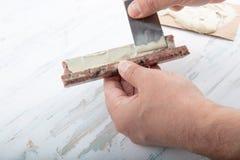 Bemannen Sie das Addieren des Klebers ein defekter Marmor mit einer Spachtel Stockfoto