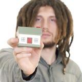 Bemannen Sie das Anhalten eines kleinen Hauses in seinen Händen lizenzfreies stockfoto