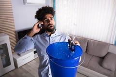 Bemannen Sie das Anrufen des Klempners While Leakage Water, das in Eimer fällt lizenzfreies stockbild