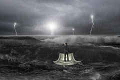 Bemannen Sie das Anstarren des Leuchtturmes auf Geldboot im Ozean mit Sturm Lizenzfreie Stockbilder