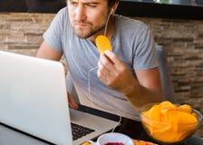 Bemannen Sie das Arbeiten am Computer und das Essen des Schnellimbisses Ungesunde Lebensdauer stockfotografie