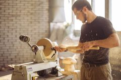 Bemannen Sie das Arbeiten an der kleinen hölzernen Drehbank, ein Handwerker schnitzt Stück Holz lizenzfreies stockfoto