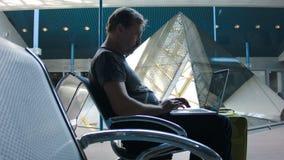 Bemannen Sie das Arbeiten an einem Laptop am Flughafen stock footage