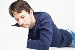 Bemannen Sie das Arbeiten an Laptop beim Legen auf den Boden Stockfotos